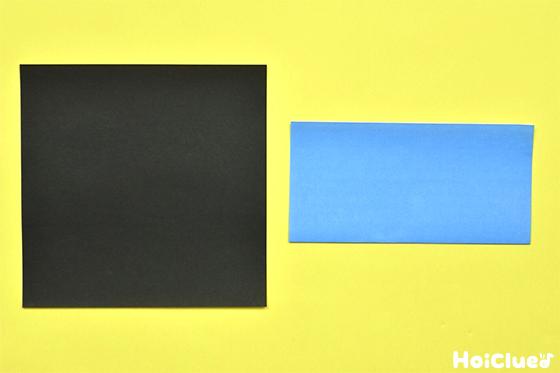 黒い折り紙と長方形に半分に折った水色の折り紙