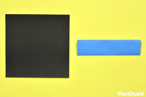黒い折り紙と更に半分に折った水色の折り紙