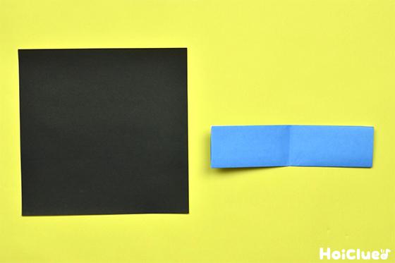 黒い折り紙と横に折った部分を開いた水色の折り紙