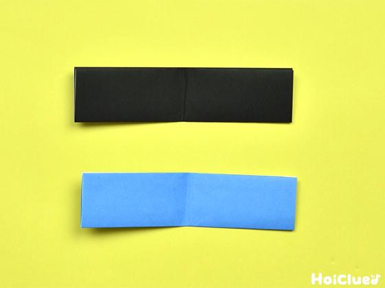 同様に折って開いた同じ形の黒と水色の折り紙