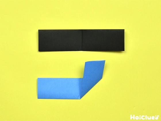 水色の折り紙を中心線を軸にして上に折り上げた様子
