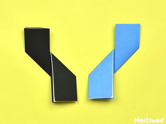 黒と水色の折り紙の折っていない側を反対方向へひねるように折った様子