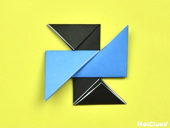 水色の折り紙と黒い折り紙を十字型に重ね合わせた様子