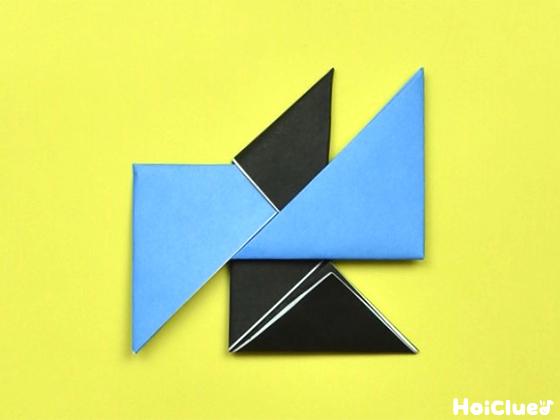 黒い折り紙の上の三角の部分を中心に向かって下に折り、水色の折り紙の中に差し込んだ様子