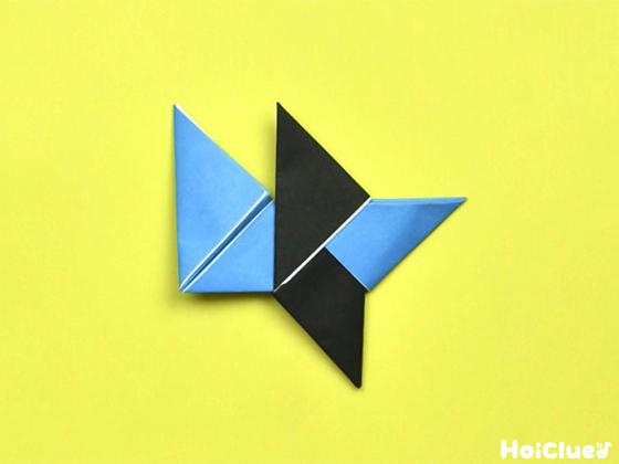 水色の折り紙の右の三角部分を中心に向かって折り黒い折り紙に差し込んだ様子