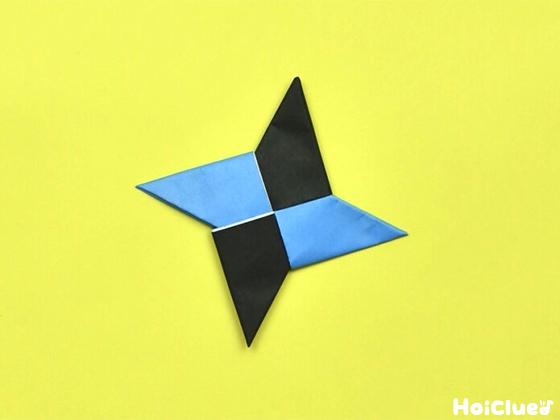 同様に水色の折り紙の左の三角を中心に向かって折り、黒い折り紙に差し込み完成した手裏剣
