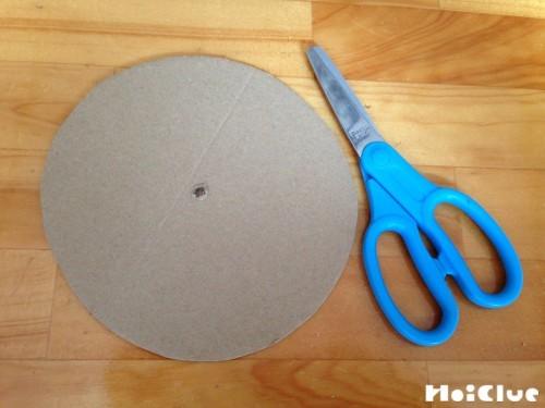 丸く切ったダンボールとハサミの写真