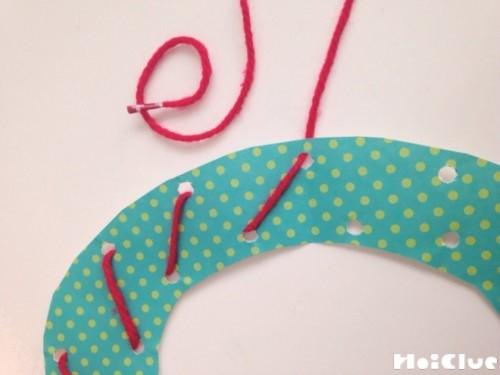ドーナツ型の画用紙に毛糸を通している写真