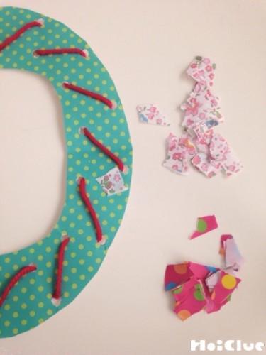 ドーナツ型の画用紙にちぎった紙を貼り付けている写真