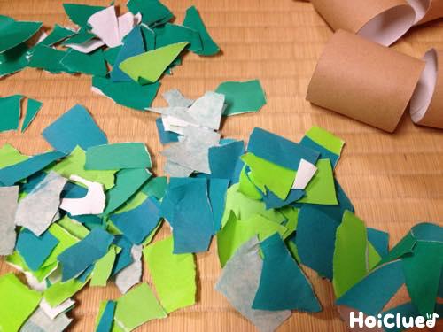 半分に切ったトイレットペーパーの芯と、ちぎった折り紙の写真