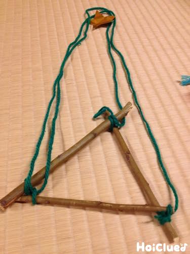 3本の木の枝を三角形に固定し毛糸をつけた様子