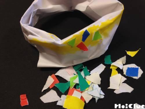 折った紙をドーナツ状に巻き絵の具で色付け折り紙を貼る様子