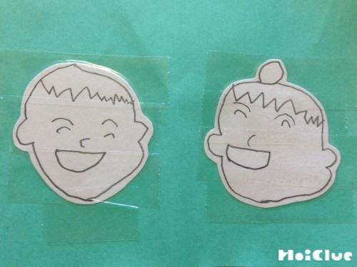 折り紙に顔を貼り付けた写真