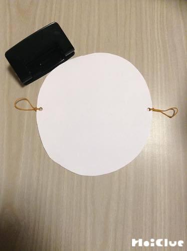 丸い画用紙の両端に輪ゴムをくくりつけた写真