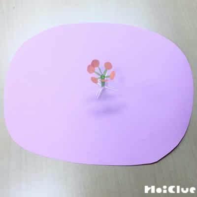 丸く切った画用紙の真ん中に画用紙で作った花芯をつけた写真