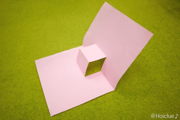 折り曲げた画用紙を開いている写真