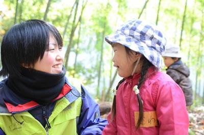 森の中で話す大人と子どもの写真