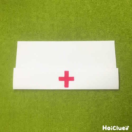 横長に置いた紙の下部を7cm折り上げ、その中心に赤い十字を描いた様子