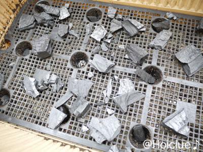 プランターの底に鉢底ネットを乗せ砕いた炭を敷いた写真