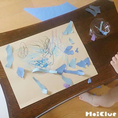 画用紙に雨の絵を描いたり貼ったりする様子