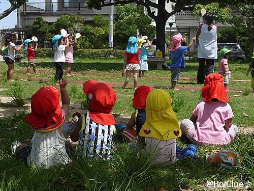 幼児たちがエイサーの練習をする様子を見つめる乳児たちの様子
