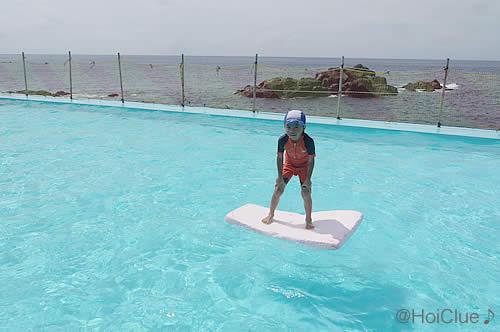 水に浮かべたボードの上に乗る子どもの様子