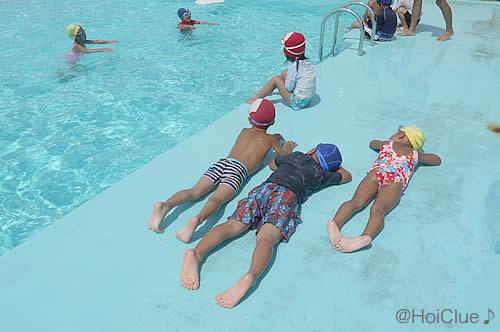 プールサイドにうつ伏せになっている子どもたちの写真