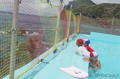 プールの中から海を見ている子どもたちの写真