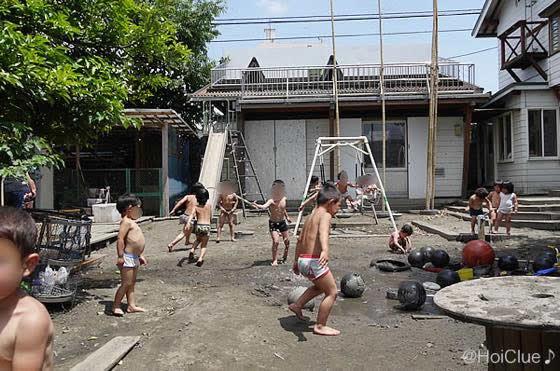 園庭でパンツ一丁になって水遊びをする子どもたちの様子