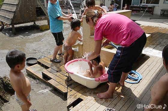 先生と一緒に水遊びをする子どもたちの様子