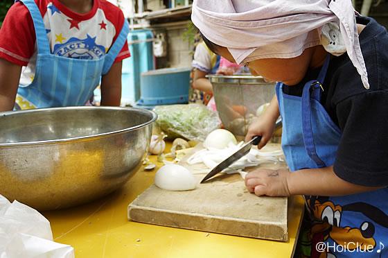 玉ねぎを包丁で切る子どもの様子