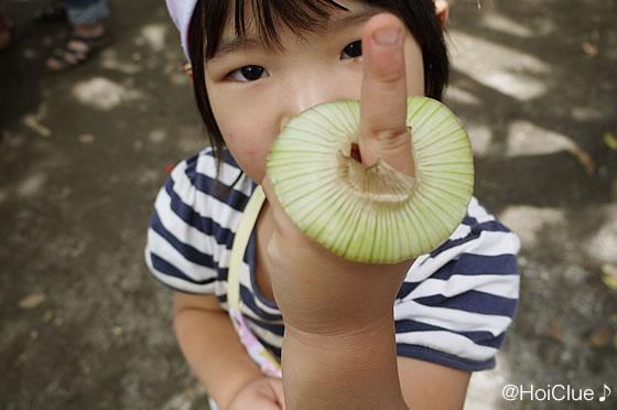 玉ねぎの輪に指を入れる子どもの写真