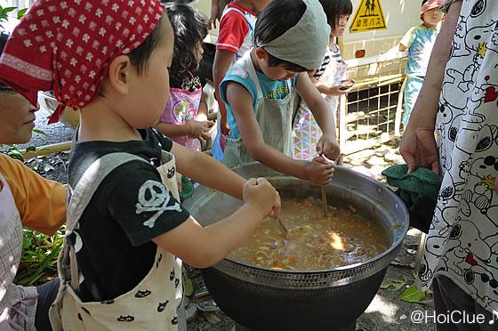 カレーの入った鍋をかき混ぜる子どもたちの様子