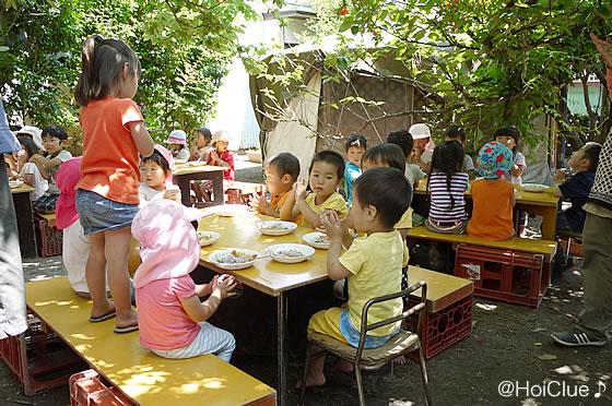 作ったカレーを庭で食べる子どもたちの様子