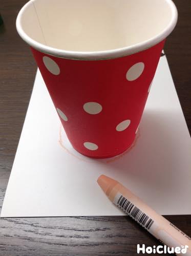 画用紙に紙コップを置き底をなぞって円を描く様子