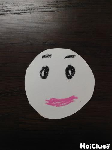 円にした画用紙にサンタさんの顔を描いた写真