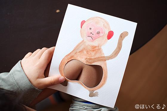 曲げた肘の内側に猿の絵を当てる様子