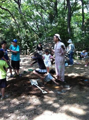 冒険遊び場(あさかプレーパーク)にて、子どもたちに泥で足を固められるプレーリーダー