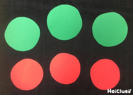 赤と緑の画用紙を丸く切った写真
