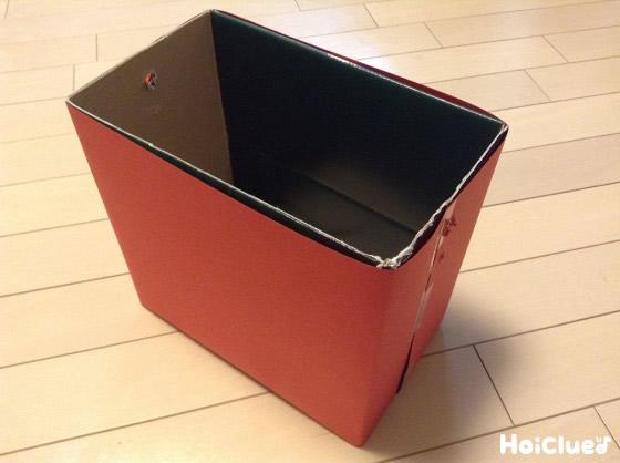 空き箱の周りを折り紙で包んている写真