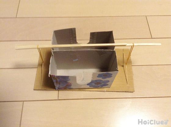 切りとったティッシュ箱を段ボールに上に置き、輪ゴムを通した割り箸で挟むようにしている写真