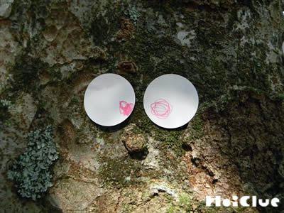 目を描いた丸い紙を木に貼った写真