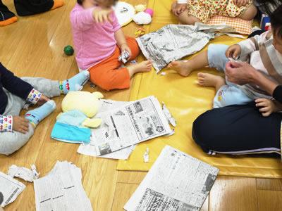 園内で新聞遊びをする子どもたちの様子