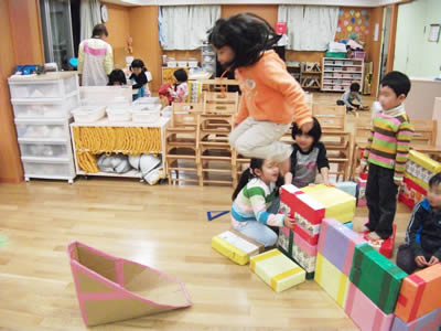 遊具からジャンプする子どもの写真