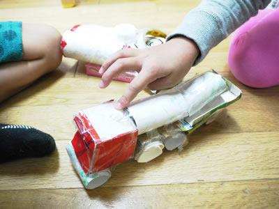 空き箱で作った車で遊ぶ子どもの写真