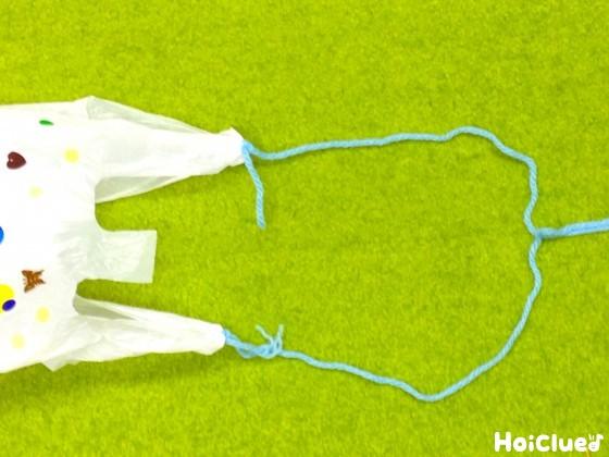 レジ袋の持ち手部分に毛糸を結びつけた写真
