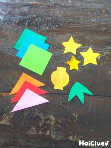 折り紙でいろいろな形を切り取っている写真