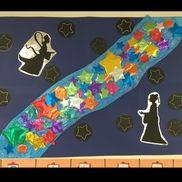 8月のカレンダー壁面。ホイル折り紙に線を描いておいて、子供たちに切ってもらいました。黒丸台紙に星型になるように穴あけておいて、刺繍糸を通す紙刺繍。シンプルに仕上がりました。