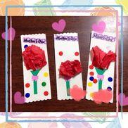 【母の日製作】・1歳児、2歳児・画用紙、折り紙、お花紙、丸しーる画用紙にあらかじめ折り紙で作った茎とリボンを貼っておく。さらに茎の上に両面テープを貼って、子どもが製作する時に外す。子どもには10センチ四方の花紙を丸めてもらい、両面テープの上に貼ってもらう。あとは丸シールを貼り付け、終了。