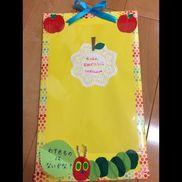 卒園児へプレゼント。時間割り入れ。2歳児。袋のところに時間割りのプリントを入れます。腹ペコあおむしはフェルトシールで子ども達が貼りました。材料・レースペーパー・画用紙・ダンボール(給食のゼリーの底板を使用)・艶紙・マスキングテープ・リボン・シール折り紙(目)